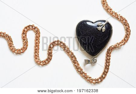 Brooch as heart near golden chain on white wooden background with free space