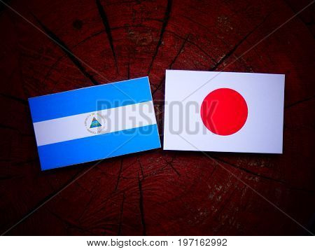 Nicaraguan Flag With Japanese Flag On A Tree Stump Isolated