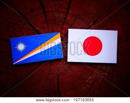 Marshall Islands Flag With Japanese Flag On A Tree Stump Isolated