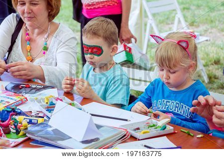 Zaporizhia/Ukraine- May 28, 2017: Charity Family festival- art and craft children activity.Boy with painted face mask and girl with funny cat ears, participating at plasticine molding workshop.