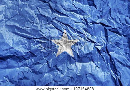 Somalia flag painted on crumpled paper background