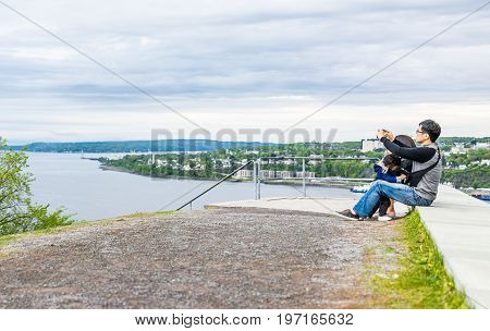 Quebec City, Canada - May 30, 2017: People Sitting High Up At Top Of Pierre Dugua De Mons Parc Des C