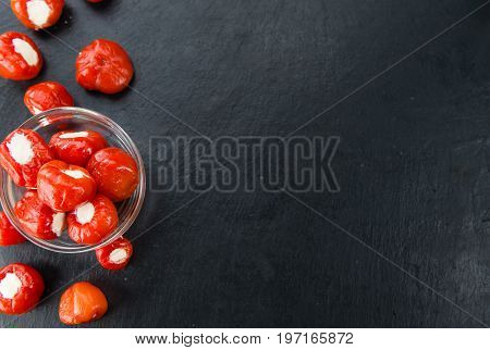 Portion of Filled Pimientos as detailed close up shot on a slate slab (selective focus)