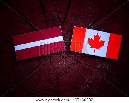 Latvian Flag With Canadian Flag On A Tree Stump Isolated