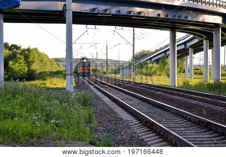 The freight train moves moving under the road overpass