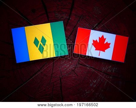 Saint Vincent And The Grenadines Flag With Canadian Flag On A Tree Stump Isolated