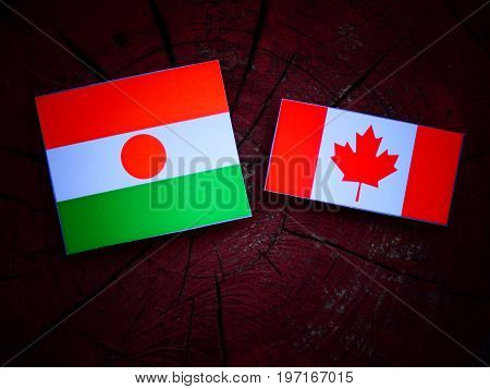 Niger Flag With Canadian Flag On A Tree Stump Isolated