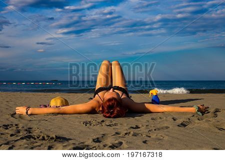 Young Good Looking Tanned Redhead Laying On A Sandy Beach With Arms Resting And Leg Resting And Happ