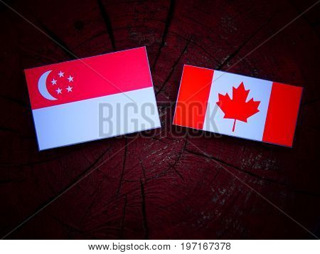 Singaporean Flag With Canadian Flag On A Tree Stump Isolated