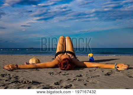 Young good looking tanned redhead laying on a sandy beach with arms resting and leg resting and happily posing with arms widespread with sun cream and hat on the side and heavenly blue sky and sea in the background during summer