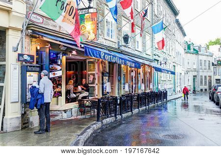Quebec City, Canada - May 31, 2017: Old Town Street Rue Couillard With Man Reading Menu Of Portofino