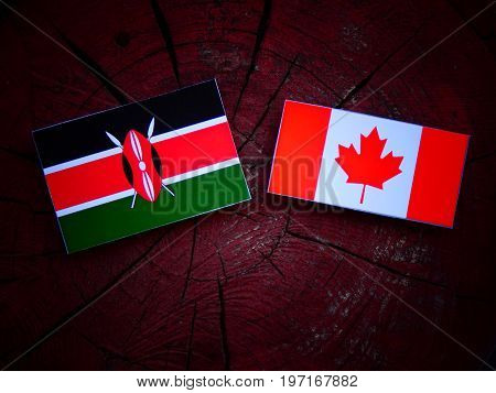 Kenyan Flag With Canadian Flag On A Tree Stump Isolated