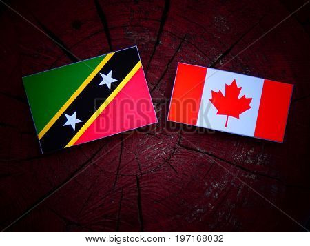 Saint Kitts And Nevis Flag With Canadian Flag On A Tree Stump Isolated