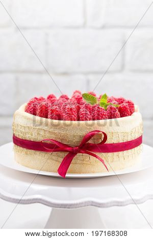 Birthday spongecake with raspberries decorated ribbon and bow on a white cake stand