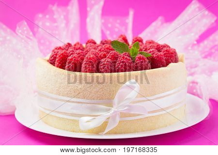 Birthday spongecake with raspberries decorated white ribbon and bow on a pink background