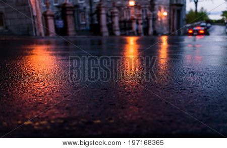 Macro Closeup Of Wet Street Pavement At Night With Reflection Of Golden Lantern Lights