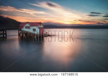 Sunset and a calm evening tide at the old lifeboat station in Mumbles, Swansea Bay, South Wales, UK