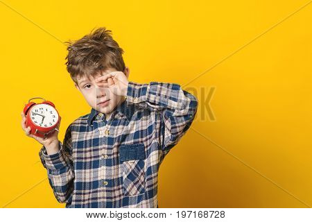 Little Boy Waking Up With Alarm Clock, Isolated On Yellow Background.