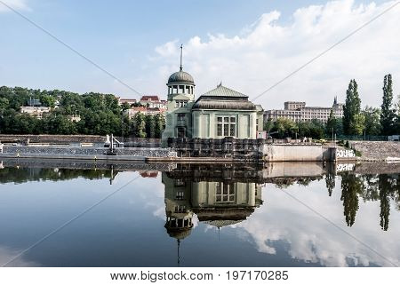 Praha Сzech republic - July 6 2017: building of Vodni elektrarna built in 1912-1913 and designed by architect Alois Dlabac on Stvanice isle reflecting on Vltava river in Prague in Czech republic during summer day with blue sky and clouds