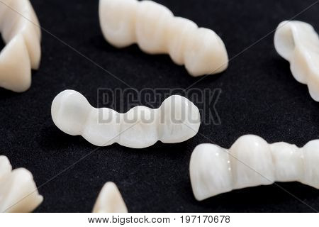 Dental ceramic or zirconium tooth bridges on dark black surface.