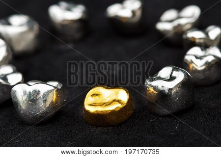 Dental gold and metal tooth crowns on dark black surface.