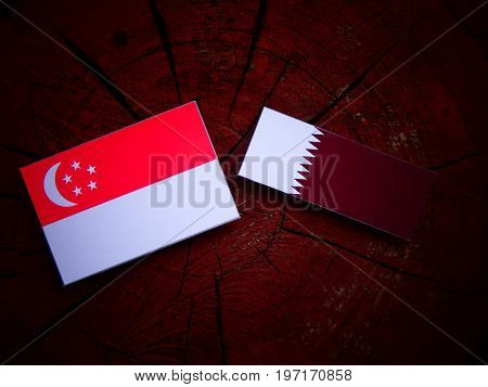 Singaporean Flag With Qatari Flag On A Tree Stump Isolated