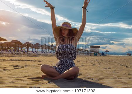 Happy Cheerful Summertime Woman Wearing Dress And Hat Sitting On The Beach With Arms Raised And Suns