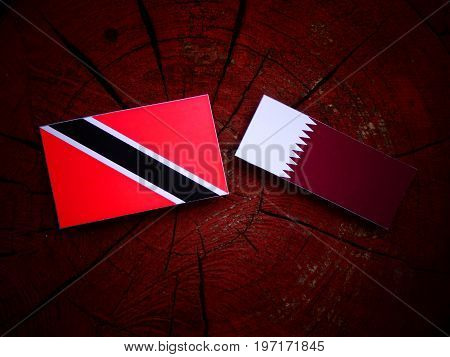 Trinidad And Tobago Flag With Qatari Flag On A Tree Stump Isolated