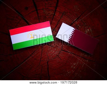 Tajikistan Flag With Qatari Flag On A Tree Stump Isolated