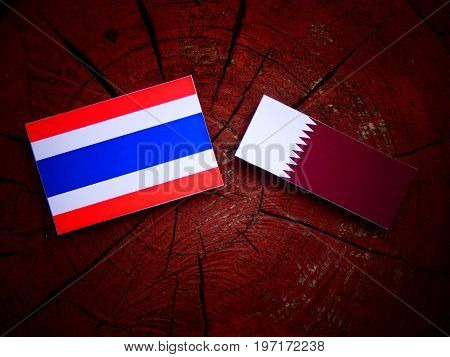 Thai Flag With Qatari Flag On A Tree Stump Isolated