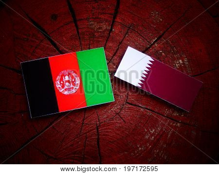 Afghani Flag With Qatari Flag On A Tree Stump Isolated