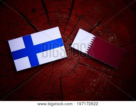 Finnish Flag With Qatari Flag On A Tree Stump Isolated