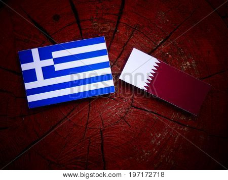 Greek Flag With Qatari Flag On A Tree Stump Isolated