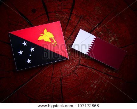 Papua New Guinea Flag With Qatari Flag On A Tree Stump Isolated