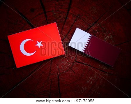 Turkish Flag With Qatari Flag On A Tree Stump Isolated