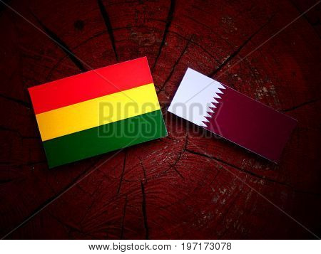 Bolivian Flag With Qatari Flag On A Tree Stump Isolated