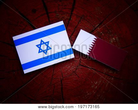 Israeli Flag With Qatari Flag On A Tree Stump Isolated