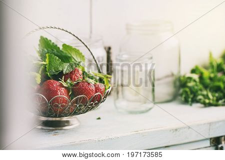 Fresh ripe garden strawberries and melissa herbs in vintage vase standing with empty glass jars for jam on blue white wooden kitchen table. Rustic style, day light, copy space. Subjective view