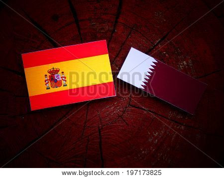 Spanish Flag With Qatari Flag On A Tree Stump Isolated