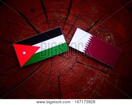 Jordanian Flag With Qatari Flag On A Tree Stump Isolated