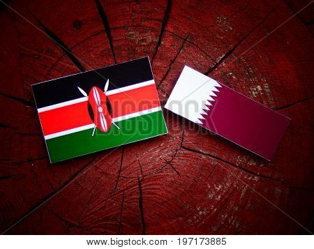 Kenyan Flag With Qatari Flag On A Tree Stump Isolated
