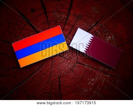 Armenian Flag With Qatari Flag On A Tree Stump Isolated