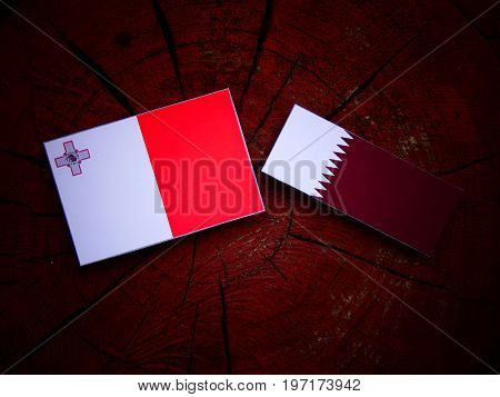 Maltese Flag With Qatari Flag On A Tree Stump Isolated