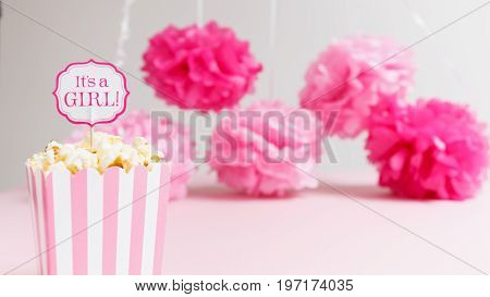 It's a girl sign in a popcorn bag at the baby shower party.  Paper flowers background. Baby shower celebration concept. Festive party background. Horizontal, wide screen format