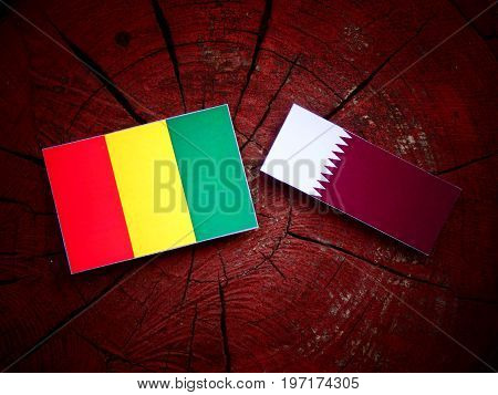 Guinean Flag With Qatari Flag On A Tree Stump Isolated