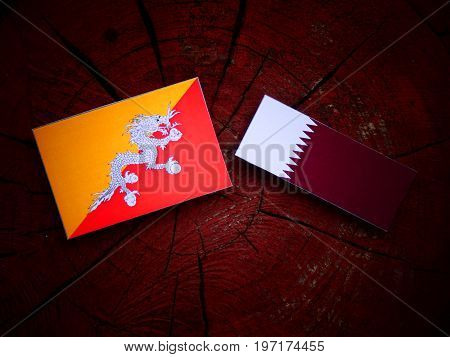 Bhutan Flag With Qatari Flag On A Tree Stump Isolated