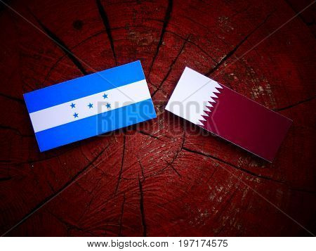 Honduran Flag With Qatari Flag On A Tree Stump Isolated