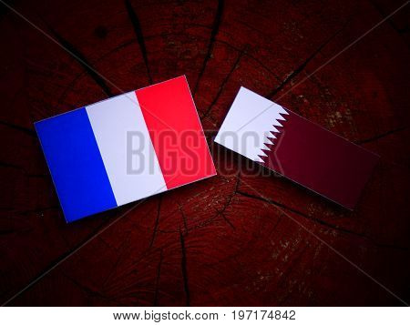 French Flag With Qatari Flag On A Tree Stump Isolated