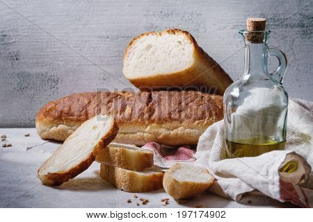 Homemade white wheat bread whole and slice served with bottle of olive oil and wheat grain seeds, white linen towel over gray texture kitchen table.
