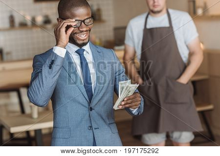 Smiling African American Businessman Holding And Counting Money, Waiter Standing Behind In Cafe